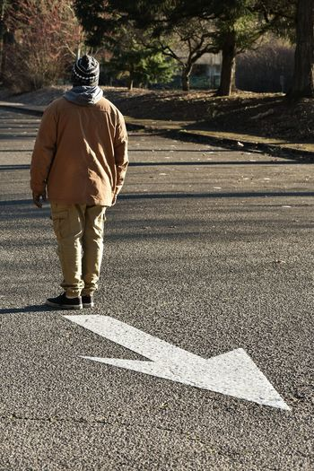 Rear view of man standing opposite to arrow sign on road