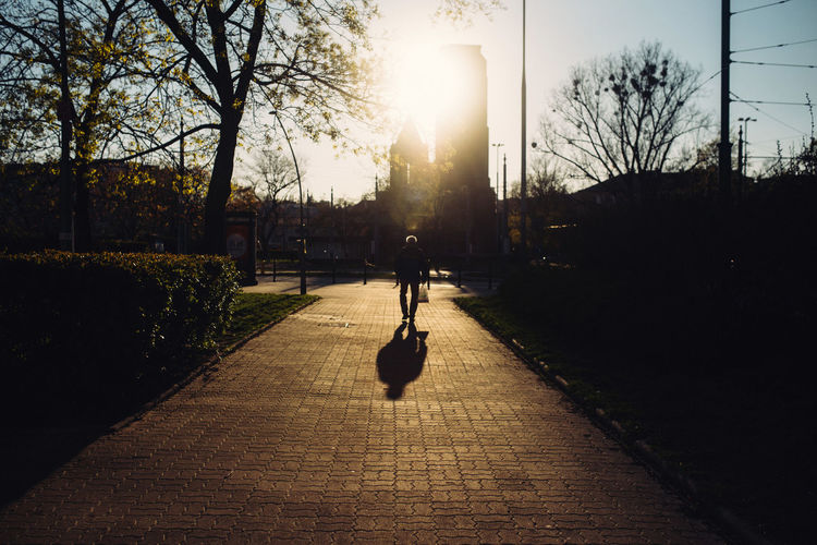 Silhouette person walking on footpath by street against sky during sunset