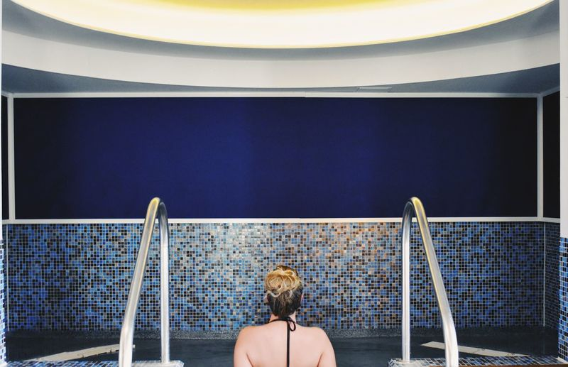 Rear view of woman sitting in a pool