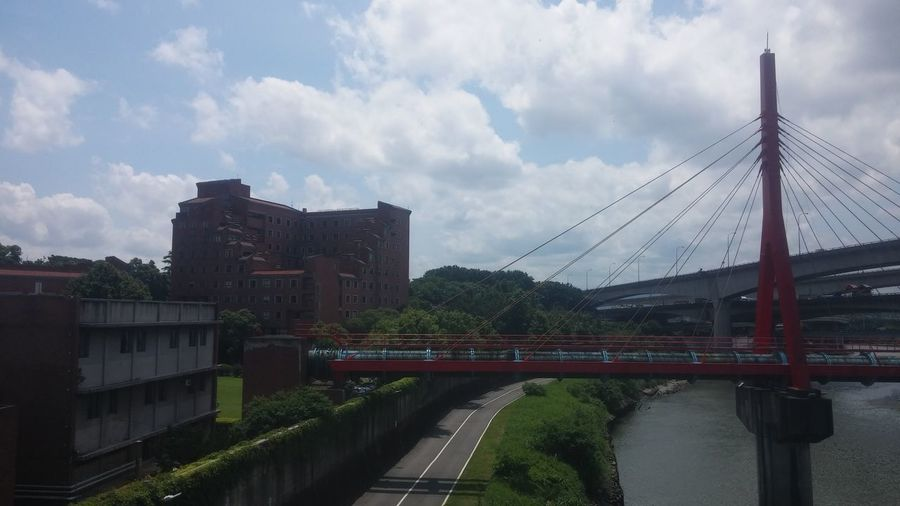 Crossing Architecture Bridge - Man Made Structure Bridges Building Exterior Built Structure City Cityscape Cloud - Sky Connection Day Engineering Exterior No People Outdoors Railway Bridge Red Bridge Red Building River Road Sky Sky And Clouds Transportation Tree Wall Water