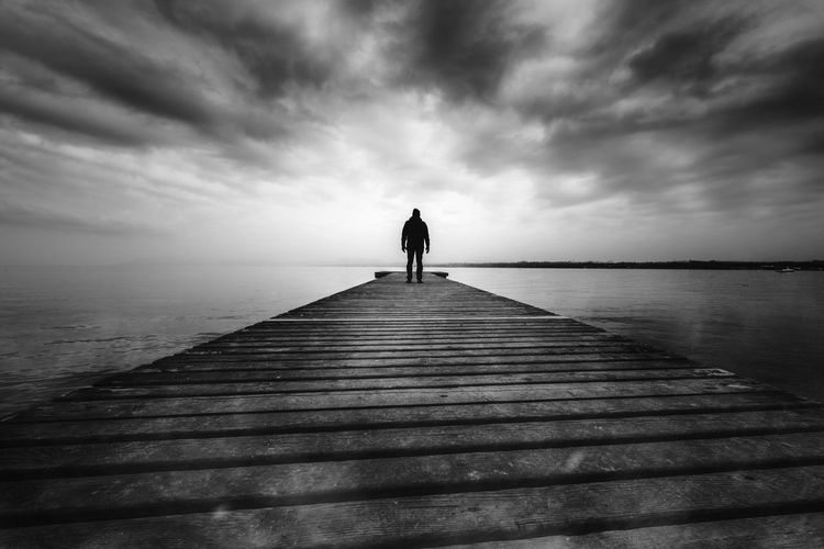 Blackandwhite Cloud - Sky Horizon Over Water Lake Nature One Person Outdoors Real People Rear View Scenics Silhouette Sky Standing Tranquil Scene Tranquility Water Wood Paneling Black And White Friday