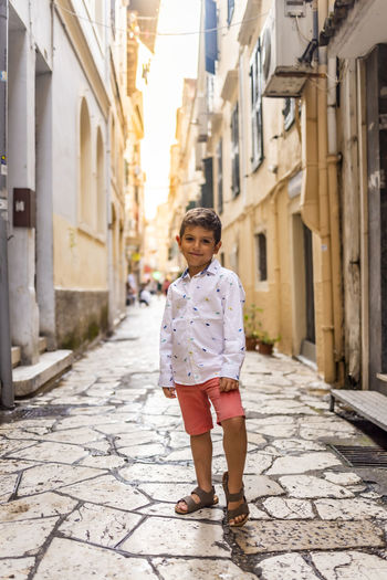 Full length portrait of boy standing on footpath amidst buildings