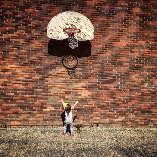 Small child playing basketball in front of brick wall