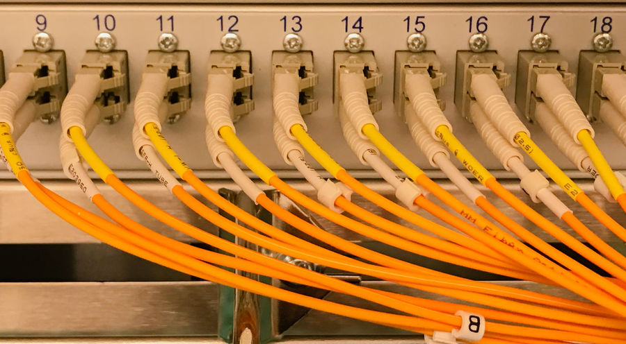 Network cable on a network HUB and Fiber optic light waveguide on a switch Data Store Patch Cable RJ45 Router Switch Cable Cable Connection Cat5 Cat6 Computer Computer Cable Concept Connection Cyberspace Data Security Ethernet Fiber Optic Cable Firewall Hub Lwl Network Network Cable Network Connection Patch Field Server