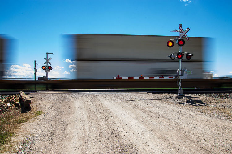 Crossing signal by railroad tracks against sky
