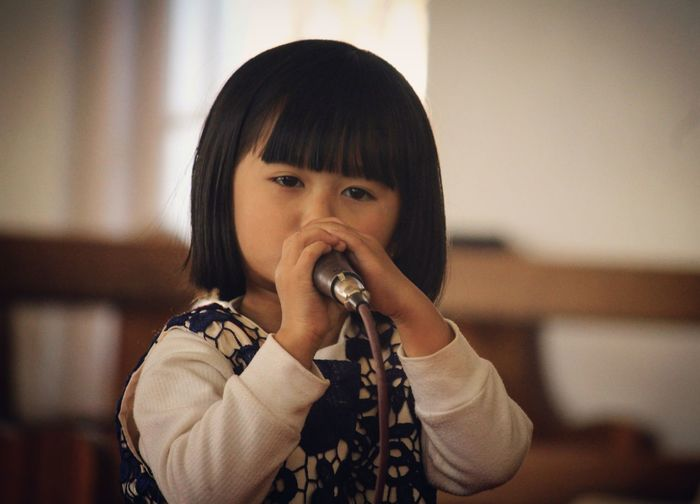 Close-Up Portrait Of Cute Girl Singing On Microphone