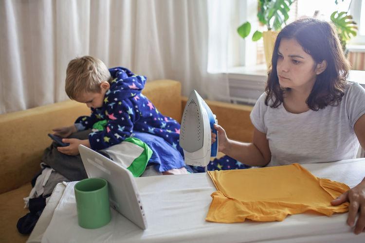 Young woman looking at camera while sitting at home