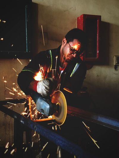 Worker Welding At Workshop