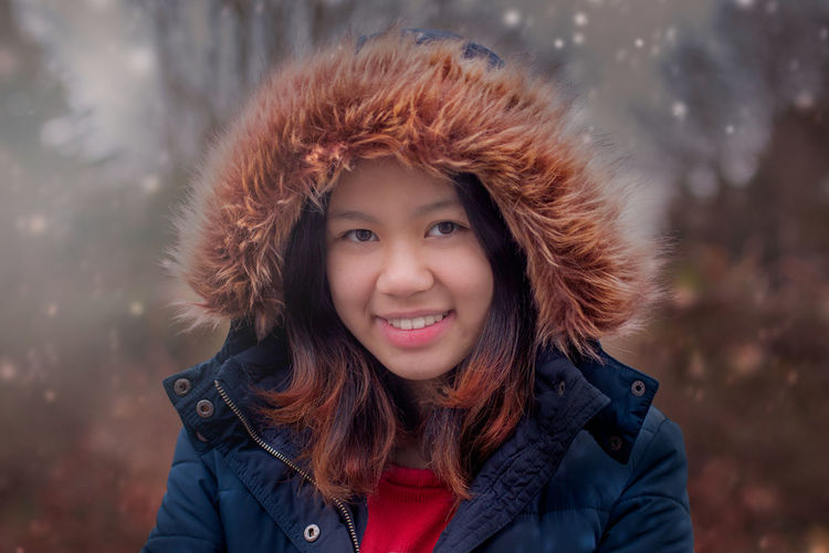 Portrait Of Smiling Woman In Fur Coat During Winter