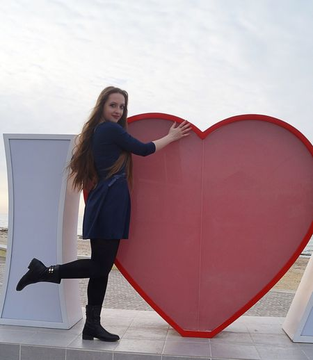 Portrait of smiling woman standing against big heart shape structure in city