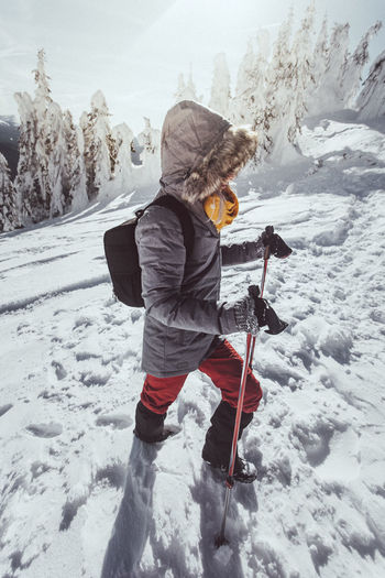 Woman is hiking in snowy winter mountains with trekkin poles and a backpack. In background blue sky and shiny sun. Concepts: adventure, determination, extreme sport. Winter Snow Cold Temperature Warm Clothing Clothing Real People One Person Full Length Mountain Leisure Activity Lifestyles Nature Child Childhood Day Beauty In Nature Covering Field Mountain Range Outdoors Snowcapped Mountain Extreme Weather Adventure Determination Concept