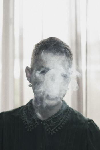 Genderblend Man Smoking Cigarette At Home