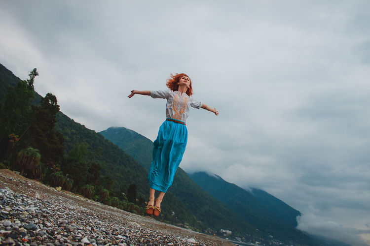 Low Angle View Of Woman Levitating Over Field By Mountain Against Cloudy Sky