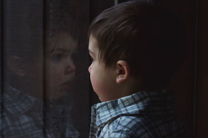 Close-up of baby boy looking though glass window