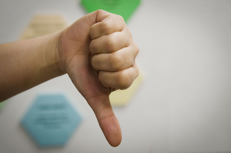 Close-up of person hand gesturing thumbs down