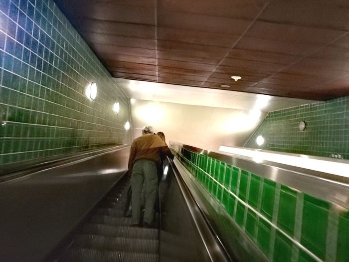 Moving up on subway station City Futuristic Illuminated Modern Rear View Journey Subway Moving Walkway  Escalator Adventures In The City