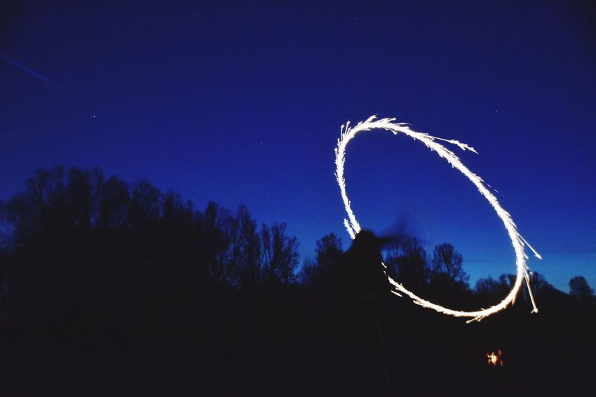 Sky Vapor Trail Blue Silhouette Low Angle View Outdoors Performance Sparkler Sparks Sparkles Ring Of Light Ring Of Fire Beauty In Nature Night Nature