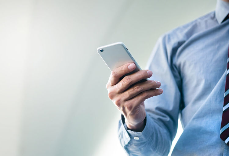 Midsection of businessman using mobile phone in city
