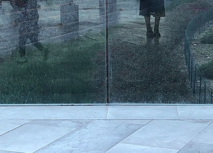 Low section of person standing on wet road during rainy season