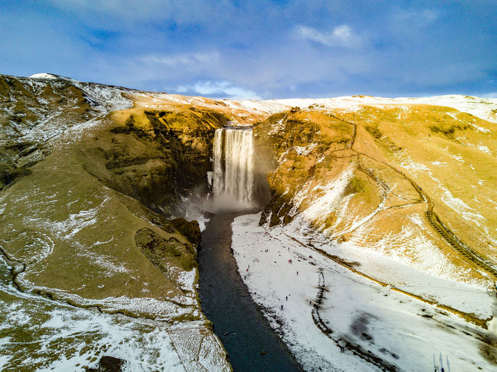 Scenic view of skogafoss against sky during winter