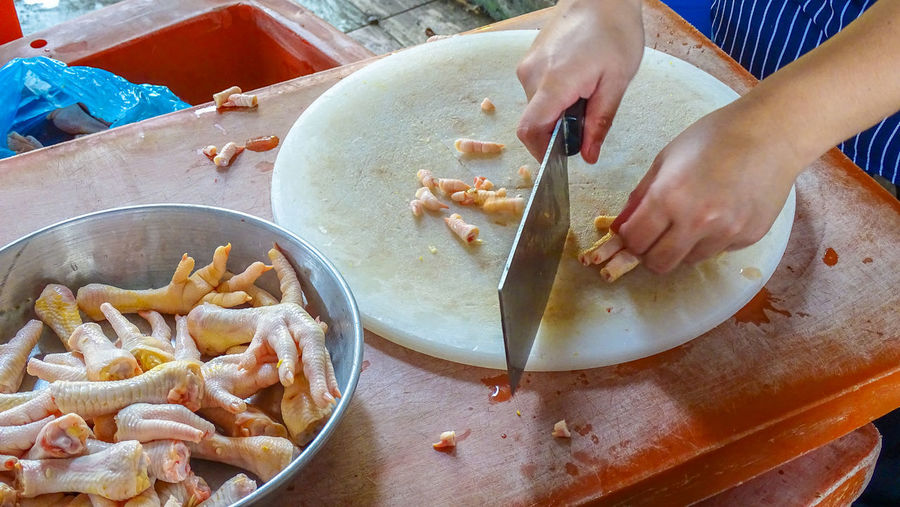 Butcher chopping raw chickens legs on a cutting board for sale in market. Butcher Chicken Chopped Cooking Dishes Chicken Leg Chopping Board Close-up Day Delicious Fillet Food Food And Drink Fresh Freshness High Angle View Indoors  Market Stall Preparation  Preparing Food Raw Chicken Real People Recipe Table Traditional Food