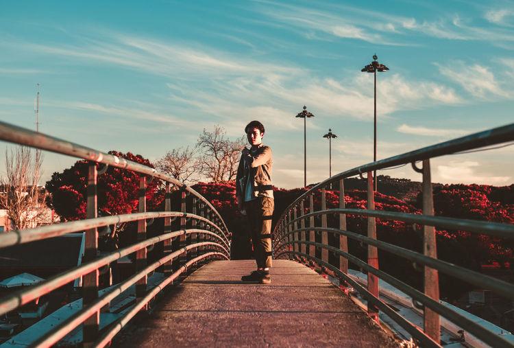Woman standing on footbridge against sky