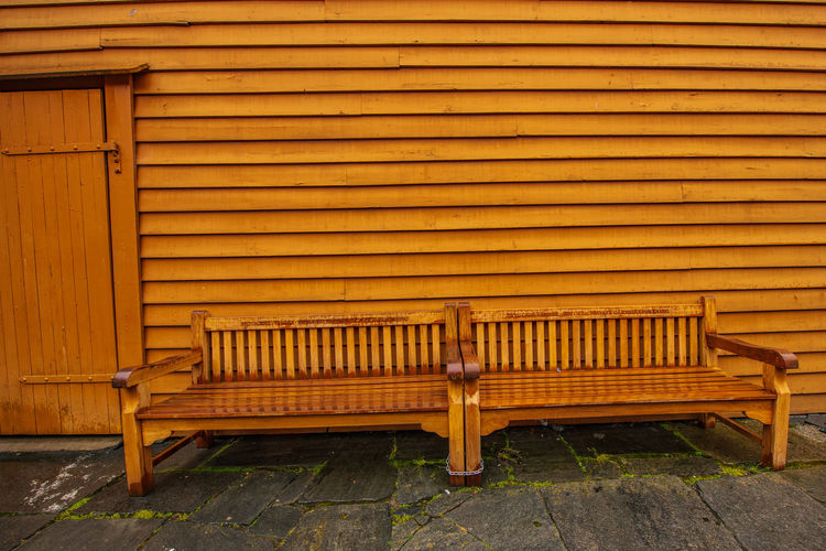 Empty bench against yellow wall