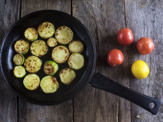 fried zucchini in a frying pan on an old weathered wooden table Frying Weathered Zucchini Background Brussels Sprout Day Directly Above Food Food And Drink Freshness Fried Fruit Healthy Eating Indoors  No People Old Pan Pod Preparation  Ready-to-eat Skillet- Cooking Pan Table Wood - Material Wooden