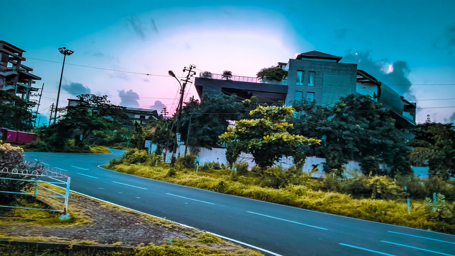 Road by buildings in city against sky at dusk