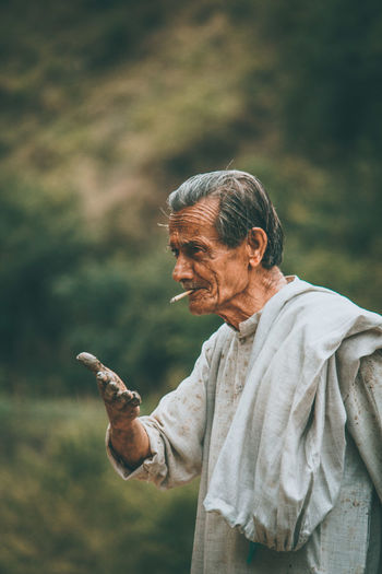 Senior man smoking cigarette while gesturing with dirty hands