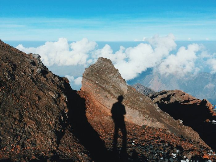 Shadow Of Man Standing On Rocky Mountain Against Sky