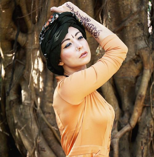 Beautiful Fashion Model Posing Against Tree Trunk