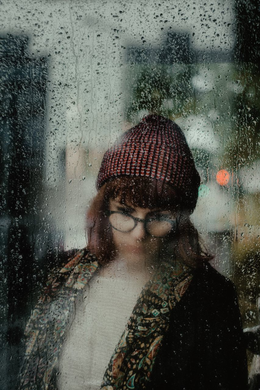Reflection Of Young Woman On Wet Glass Window