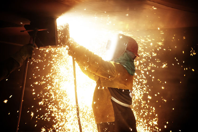 Man working on fire at night