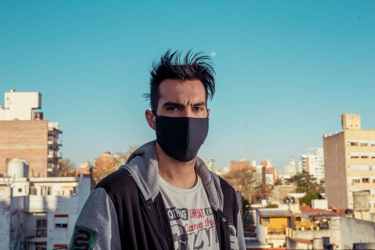 Portrait of young man with face mask in city against clear sky