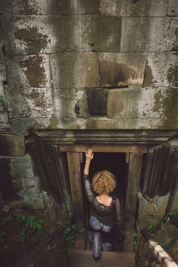 Rear View Of Woman Entering In Old Ruin