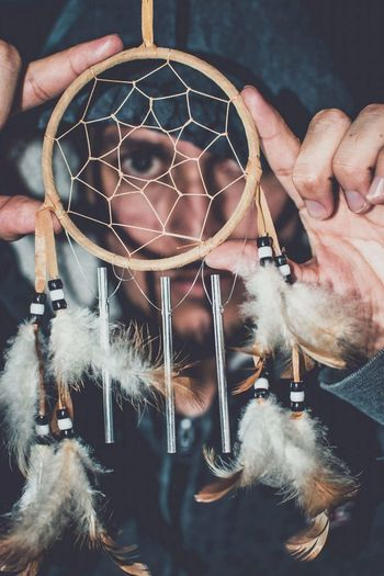 High Angle Portrait Of Young Man Looking Through Dreamcatcher