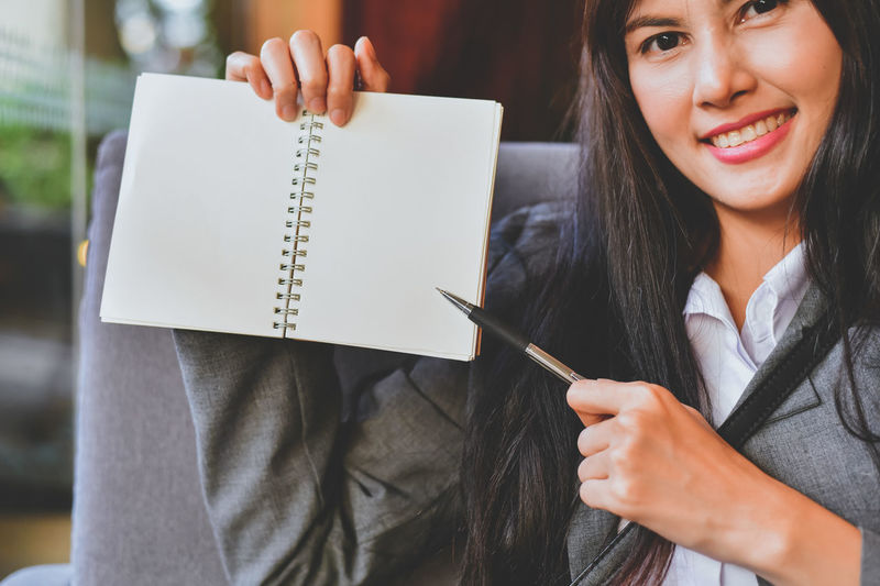 Portrait of businesswoman showing blank book while sitting in office