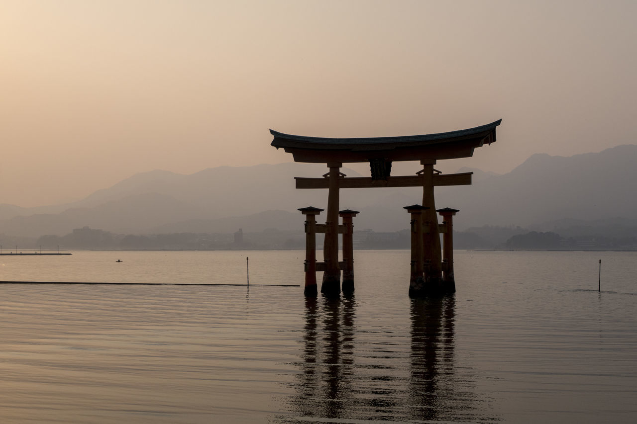 water, religion, belief, sky, spirituality, mountain, waterfront, tranquility, tranquil scene, beauty in nature, architecture, place of worship, scenics - nature, sunset, built structure, no people, nature, lake, non-urban scene, shrine, outdoors, wooden post