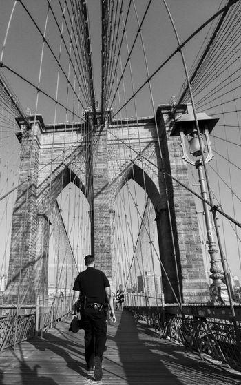 Rear view of man walking on suspension bridge