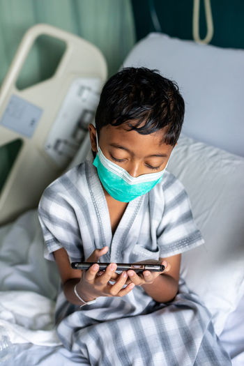 Boy using mobile phone on bed