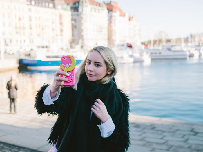 Portrait Of Young Woman Holding Mobile Phone