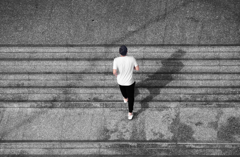 High angle view of man moving up on steps
