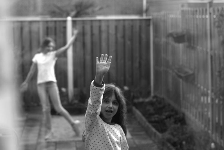 Portrait of girl waving while standing in yard