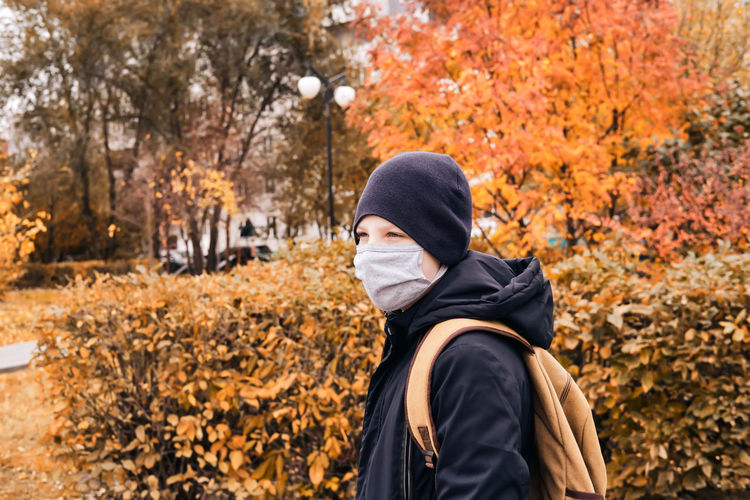 Boy wearing mask looking away while standing against autumn plants