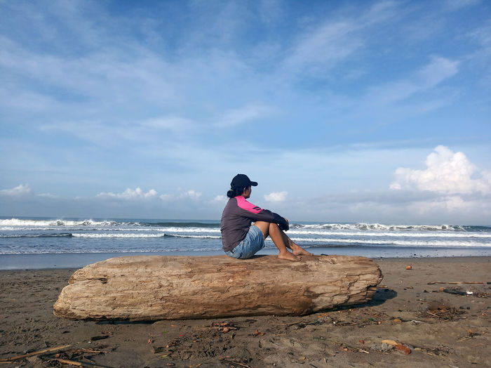 Person sitting on rock at beach against sky