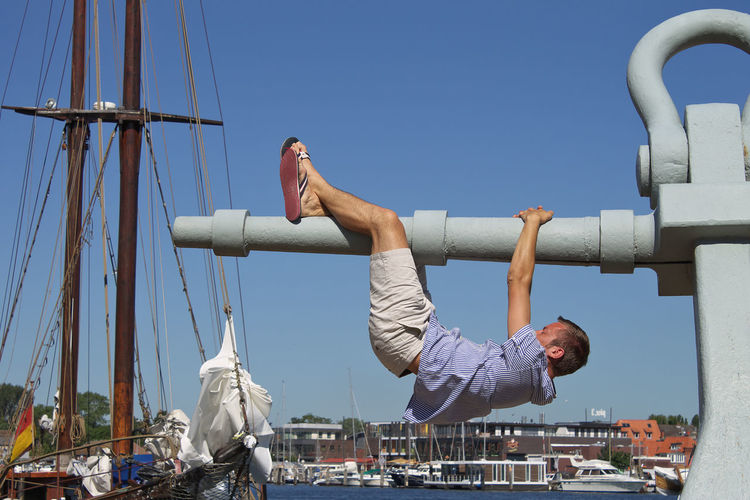 Side view of man hanging from anchor at harbor against clear sky