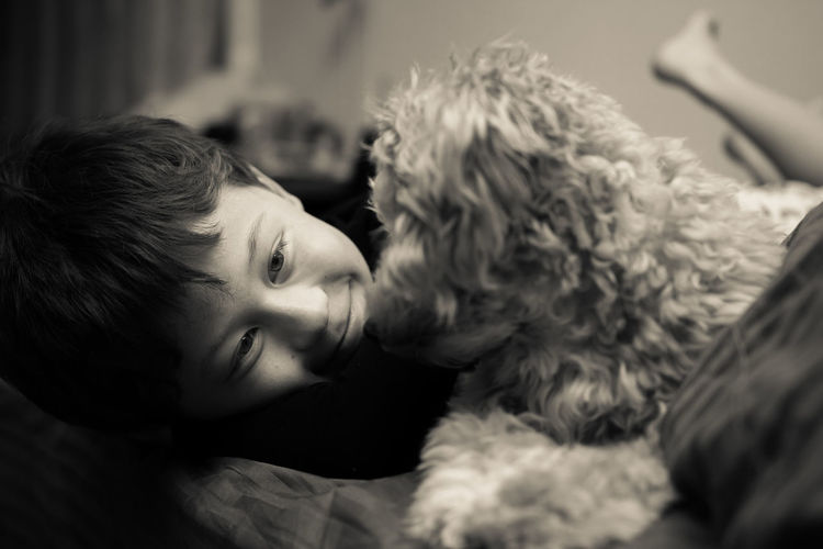 Smiling Boy With Puppy On Bed