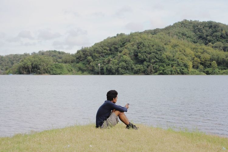 Rear view of man sitting by lake against trees