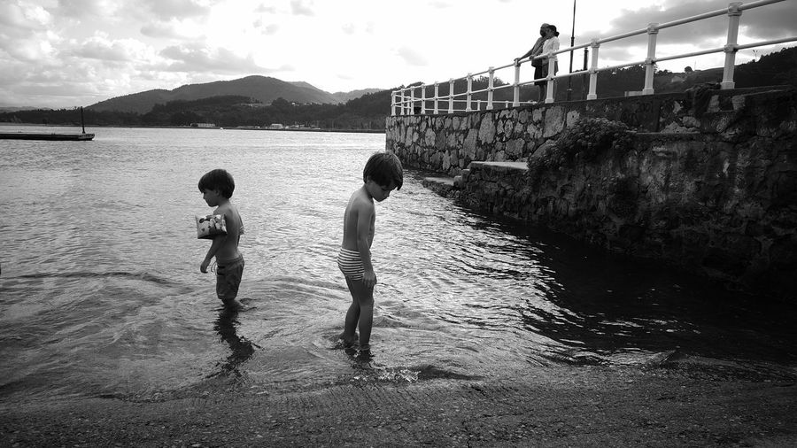 Rear view of two boys standing on riverbank